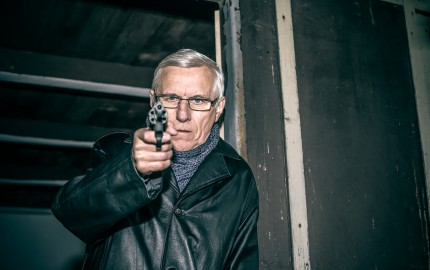 Dangerous senior man aiming a gun at you and standing in old dark cabin.