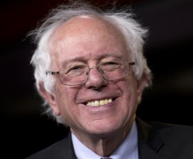 """Sen. Bernie Sanders, I-Vt., smiles as he is asked about running for president during a news conference on Capitol Hill in Washington, Wednesday, April 29, 2015. Sanders will announce his plans to seek the Democratic nomination for president on Thursday, presenting a liberal challenge to Hillary Rodham Clinton. Sanders, an independent who describes himself as a """"democratic socialist,"""" will follow a statement with a major campaign kickoff in his home state in several weeks. Two people familiar with his announcement spoke to The Associated Press under condition of anonymity to describe internal planning. (AP Photo/Carolyn Kaster)"""