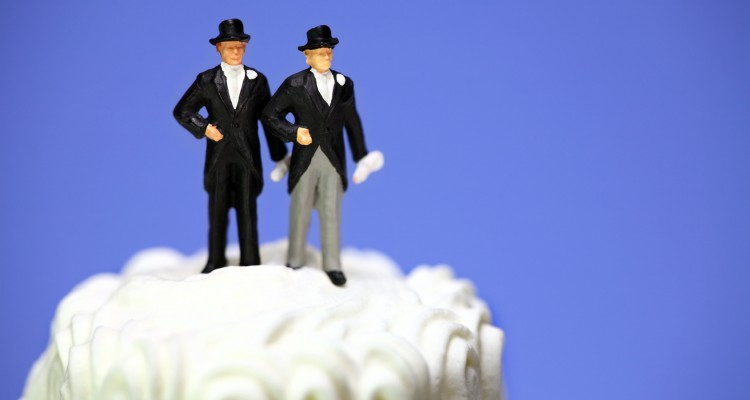Miniature homosexual couple standing on top of a wedding cake. Gay marriage concept.