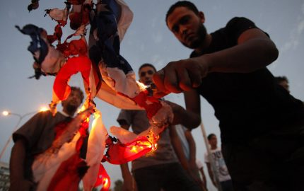 "Libyan followers of Ansar al-Shariah Brigades burn the U.S. flag during a protest in front of the Tibesti Hotel, in Benghazi, Libya, Friday, Sept. 14, 2012, as part of widespread anger across the Muslim world about a film ridiculing Islam's Prophet Muhammad.  Around 150 members of Ansar al-Shariah Brigades chanted "" Obama, Obama, we are all Osama."" (AP Photo / Mohammad Hannon)"