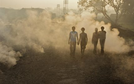Local people in Aina village and toxic fumes rising from the ground caused by burning coal at the nearby Jharia coal mine. Jharia is one of the most important coal mines in India and one of the largest in Asia. Once a treasure trove of high-quality coking coal, uncontrollable fires have turned the mine and the surroundings into a slow-burning inferno. Before coal was unearthed in this area, Jharia was a belt of dense forests inhabited by tribes.