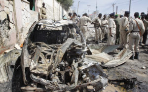 Somali soldiers stand by wreckage at the scene of a suicide car bomb attack that targeted a United Nations convoy, outside the airport in Mogadishu, Somalia Wednesday, Dec. 3, 2014. A Somali police officer says a suicide bomber rammed his vehicle into a U.N. convoy near Mogadishu's airport, killing three people. (AP Photo/Farah Abdi Warsameh)