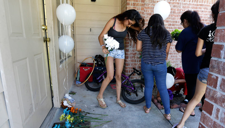 Photo from Associated Press. People place flowers and balloons at a house in Houston, Texas, on Aug. 9, 2015, where eight people were killed.